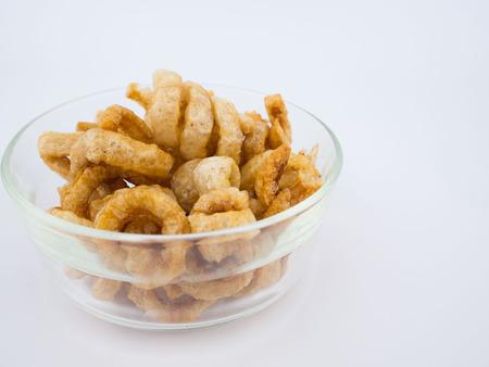 Crispy deep fried pork skin or pork rind in bowl isolated on white background Stock Photo
