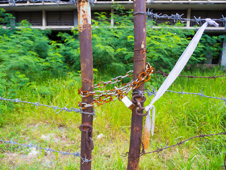 Old rusty barbed wire fence locked by master key and chain