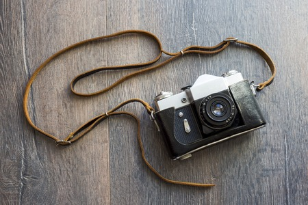 old photograph: top view of retro camera on wooden table