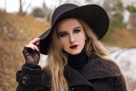 Portrait of a young beautiful woman in black hat retro style. Mysterious mystical mood. Outdoor shot. Winter season, cold weather.