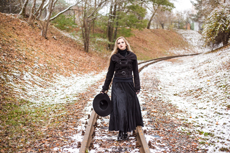 Woman in long black dress and hat walking on railway tracks. Winter. Cold weather. Travel alone.
