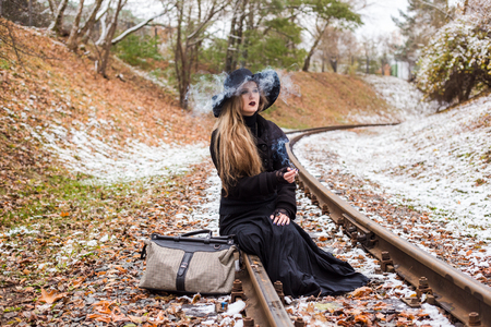 Young woman in a long black dress and hat smoking a cigarette while sitting on railroad tracks waiting for a train. The concept of loneliness and expectations. Travel alone.