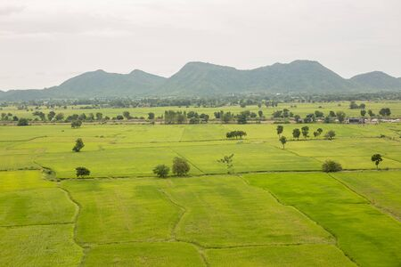 Landscape of a beautiful green rice paddy field and mountains. Kanchanaburi Province, Thailand. 免版税图像
