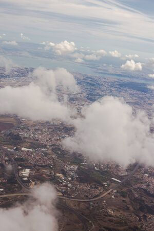 View from the porthole of an airplane. Clouds over Lisbon. Portugal