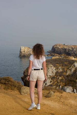 Young woman looking at Papoa cliffs and Atlantic ocean in Peniche. Beautiful rocks blue sky and sea. Tourist attraction. Portugal