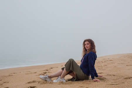 Young woman sits on sand beach. Sea in dense fog, autumn day. Foggy weather at Nazare Portugal. Atlantic ocean.