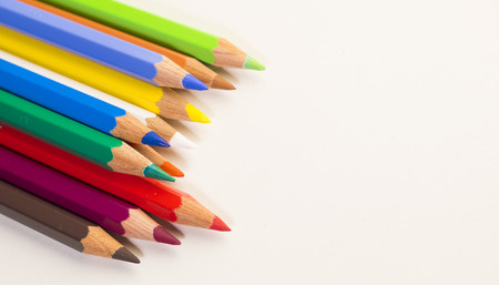Colored pencils laying in left corner on white background
