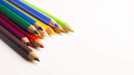 Colored pencils laying on top of eachother on white background