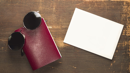 Blank red passport and round sunglasses with a blank post card on a wooden background