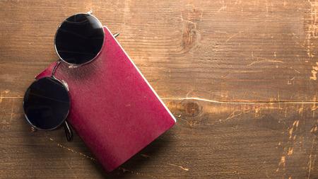 Leeg paspoort en ronde zonnebril met zwarte glazen op een houten achtergrond Stockfoto - 93509737