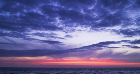 a beautiful sunset sky in the evening with intense pink and red colors transitioning in blue and purple.