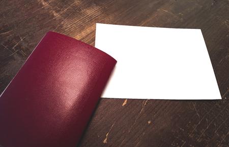 Leeg rood reispaspoort en lege witte prentbriefkaar met ruimte voor tekst en afbeeldingen. Stockfoto - 93566201
