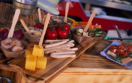 Een houten fingerfood-snack met voedsel zoals kaas, tomaten en soepen en containers met mayonaisesaus en andere heerlijke snacks Stockfoto - 93563461