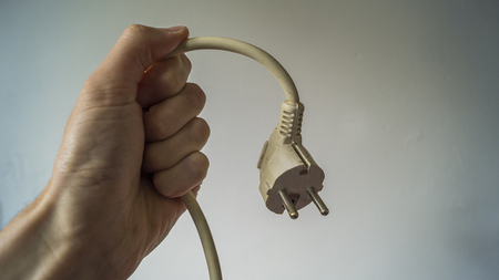 a caucassian male hand holding a electric plug unplugged against a white background Stockfoto