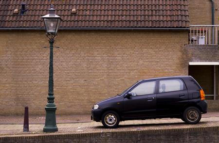Een kleine zwarte auto geparkeerd in de stoep naast een lantaarn op een ietwat steile heuvel Stockfoto - 93896251
