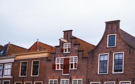 Oude traditionele huizen met oude daken tegen een achtergrond van witte wolken Stockfoto - 93561457