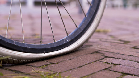 a flat broken down bicycle tire close up on a brick walkway
