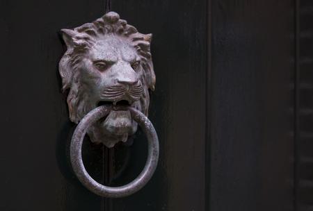 Een oude stalen leeuwvormige deurklopper met een metalen ring in zijn mond hangend aan een houten deur Stockfoto - 93507330