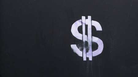 a white dollar money sign with two vertical streaks sprayed on a black wooden board and copy space