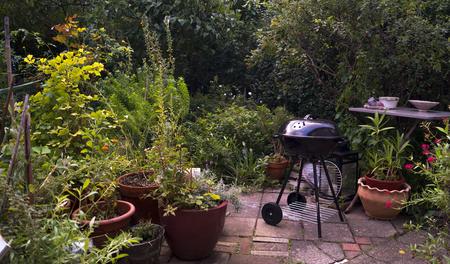Een achtertuin vulde veel groene planten, plantenpotten, struiken, bloemen en een tafel op een bakstenen vloer. Stockfoto - 93507345