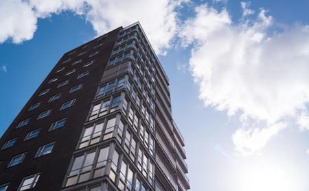 Een hoog wolkenkrabber appartementencomplex met witte wolken en een blauwe lucht met zonneschijn Stockfoto - 93509749