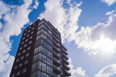 a high skyscraper apartment complex with white clouds and blue sky with sunshine
