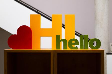 Een groot geel Hallo teken met een klein rood hart op een witte achtergrond Stockfoto - 93507353