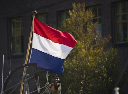 Een Nederlandse vlag wapperend in de wind met de kleuren rood, blauw en wit met een wazige boom op de achtergrond. Stockfoto - 93545762
