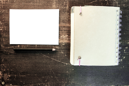a blank white postcard and a black pencil next to a blank notebook on a wooden background Stockfoto