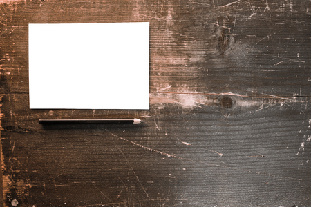 a blank white postcard with a black pencil on a wooden background