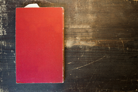 a red blank book template on a wooden table background.