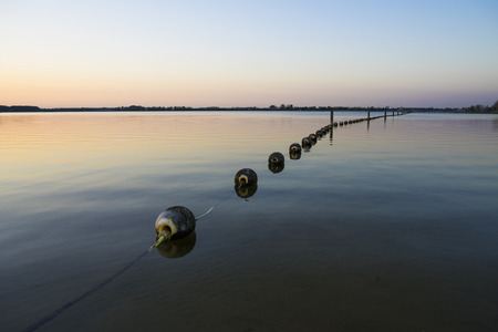 a silent and peaceful lake at dusk / sunset stretched out across the horizon with a line of buoys floating on the water Stockfoto