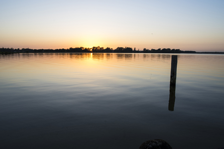 a beautiful sundown / sunset over a lake with a sun behind the trees in the distance Stockfoto