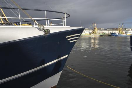 Een trawler in de haven van de haven van IJmuiden met op de achtergrond de haven en verschillende andere vissersboten. Stockfoto - 93517943