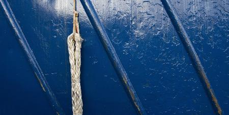 A up close photo of a rope and a blue painted metal rough surface texture