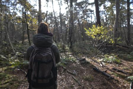 Een jonge blanke vrouw in het bos met een rugzak op en het verkennen van het bos Stockfoto - 93514747