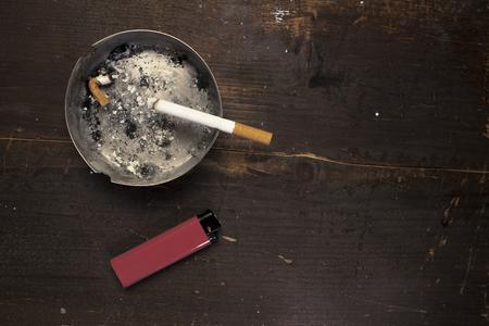 Een verlichte sigaret in een asbak met een rode aansteker eronder is op een houten achtergrond met copyspace aan de rechterkant Stockfoto - 93517941