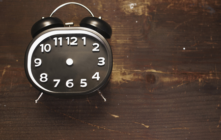 a black and white vintage alarm clock laying on a wooden background Stockfoto