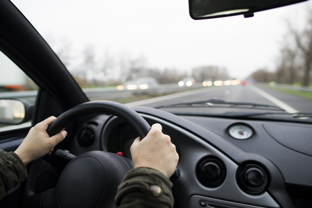 female hands holding the steering wheel of a car