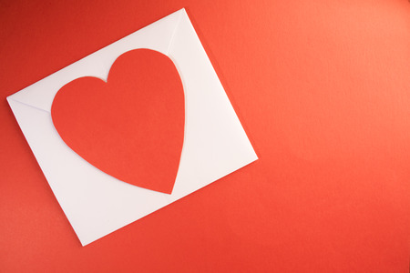 a white envelope with a bright red paper heart ontop of it against a white background template Stockfoto