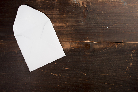 a blank empty card envelop on a wooden table background with copyspace to the left Stockfoto