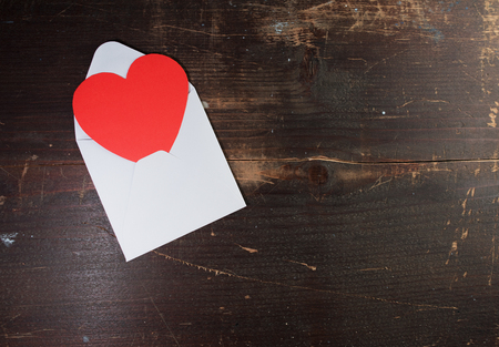a valentine envelope card with a paper heart sticking out of it on a wooden texture background