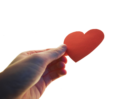 a caussian hand holding a bright red paper love heart isolated on a white background Stockfoto