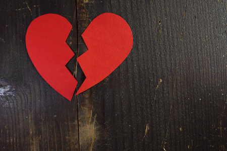 a broken torn heart of red paper on a wooden background