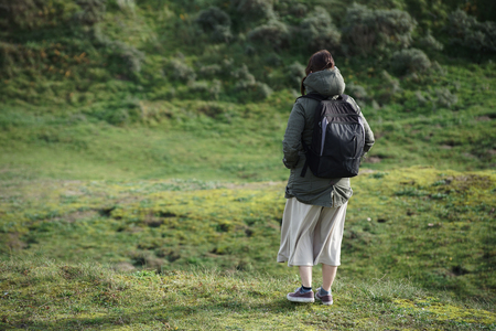 a young caucasian woman standing on a grassy hill by herself with a backpack on and a long skirt on looking into the distance ready to explore the land