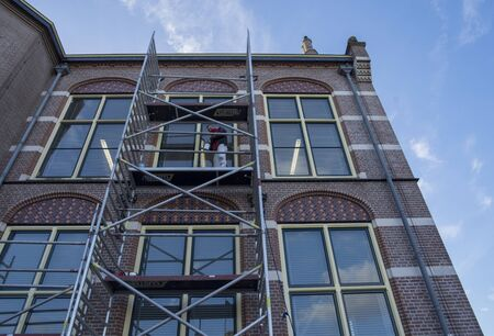 Leiden / The Netherlands - February 7 2018 - a construction worker working on a old building up on the building scaffolding in the city of Leiden Redactioneel