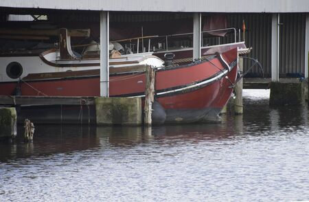 Leiden / The Netherlands - February 7 2018 - a old boat laying peacefull and quiet on a dock in a harbor near the city of Leiden