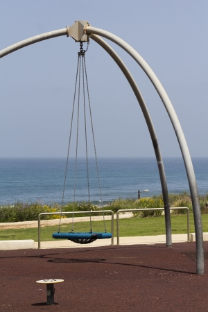 swing for children on the background of the sea photo