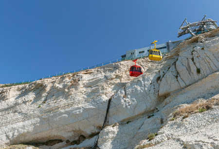 hanikra: funicular with yellow and red cabin on white background rock