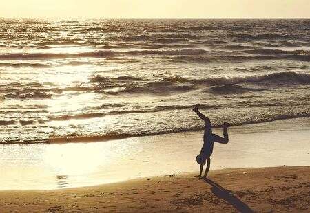 silhouette of a child upside down on the beach at sunset